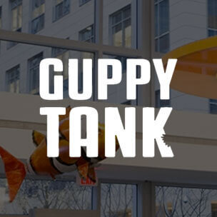 Guppy Tank text overlaid on an event image from the LabCentral lobby.