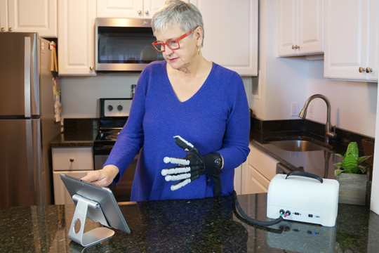 A person stands in their kitchen while wearing the soft robotic glove.